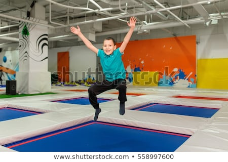 Young Boy 6 year old Jumping on a trampoline in children fitness gym Stock photo © galitskaya