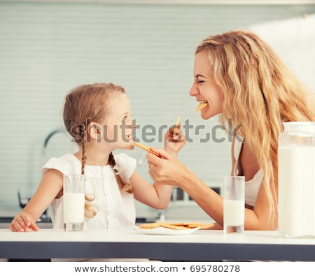Beautiful cheerful blonde woman eating biscuits. Stock photo © justinb