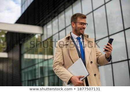 mosolyog · tanár · telefon · kabát · szemüveg · néz - stock fotó © feelphotoart