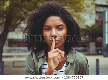 beauty portrait of attractive woman making a hush gesture stock photo © deandrobot