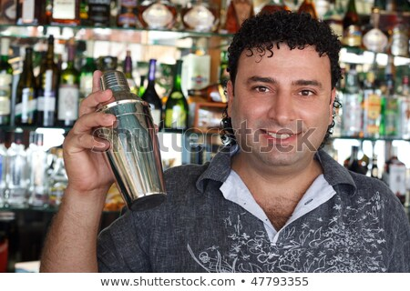 Barman with shaker behind bar rack. Smiling man against shelves with bottles. Stock photo © Paha_L