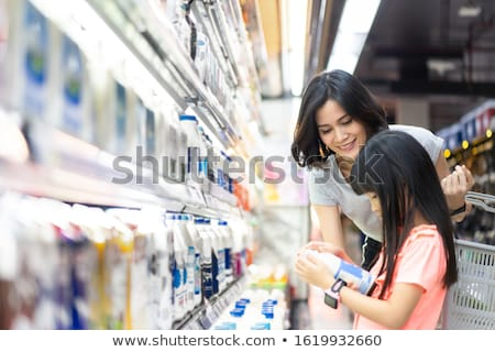 Woman with basket choosing and buying yoghurt in supermarket Stock photo © deandrobot