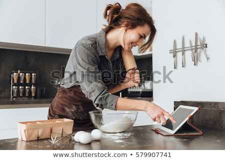 lady looking at tablet and cooking stock photo © deandrobot