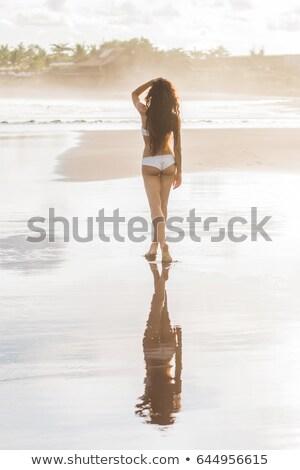 Happy slim tan women are walking on the beach in sunset Stock photo © dashapetrenko