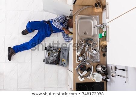 Handyman Lying On Floor Repairing Sink In Kitchen Stock photo © AndreyPopov