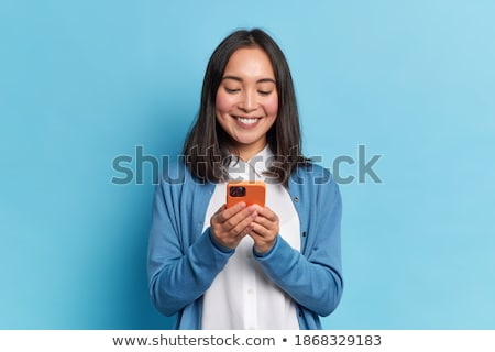 Asian beautiful woman isolated over blue background talking by mobile phone waving. Stock photo © deandrobot