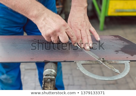Metalworker with angle meter measuring strip of metal Сток-фото © Kzenon