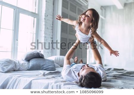 Happy father and daughter having fun together on a bed Stock photo © Lopolo