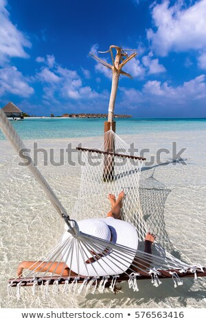 Woman Relaxing On Hammock Over The Idyllic Beach Stock photo © AndreyPopov