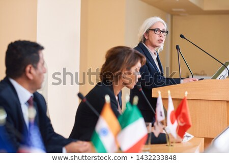 Confident female delegate in formalwear standing by tribune Stock photo © pressmaster
