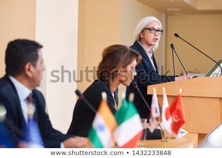 Confident female delegate in formalwear standing by tribune Stock photo © pressmaster