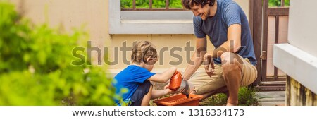 Father and son gardening in the garden near the house BANNER, LONG FORMAT Stock photo © galitskaya
