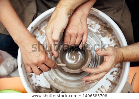 Top view at senior woman spinning clay on a wheel with teacher a Stock photo © boggy