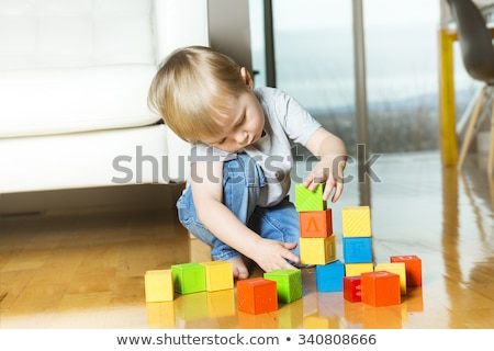 kid playing toy blocks inside his house Stock photo © Lopolo