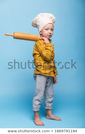 Cute little boy in apron and chef hat holding rolling-pin and looking at you Stock photo © pressmaster