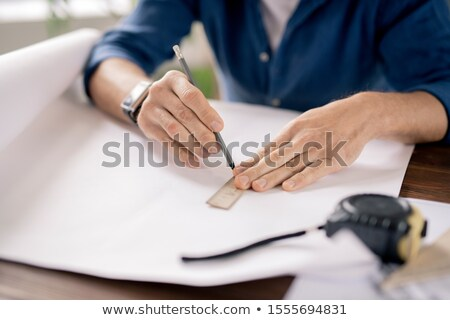Hands of mature engineer holding pencil and ruler while drawing line on paper Stock photo © pressmaster