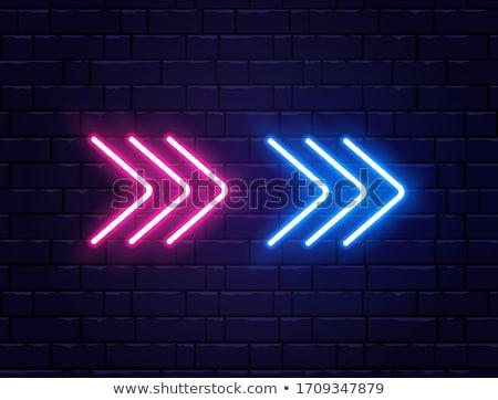 Bright blue neon glowing arrow pointer on dark brick wall Stock photo © evgeny89