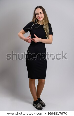 Attractive smiling teenager standing upright with a hand on her hip while holding her hat Stock photo © wavebreak_media