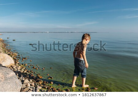boy in the ocean stands in beautiful clear water Stock photo © meinzahn