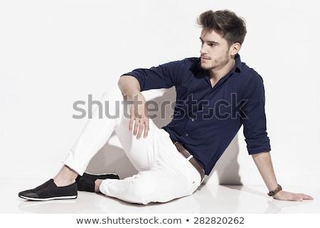 serious young fashion man sitting stock photo © feedough