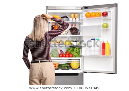 young woman posing in front of an open fridge stock photo © dash