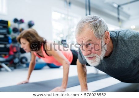 Fitness man doing exercises for arms muscles in gym Stock photo © deandrobot