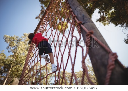 Kid climbing a rope during obstacle course training Stock photo © wavebreak_media