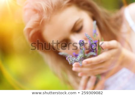 close up of beautiful young woman smelling flower stock photo © dolgachov