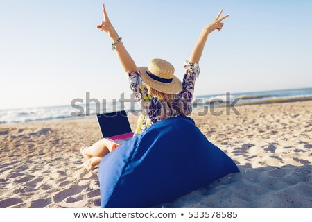 Woman in Straw Hat Works on Laprop at Beach Stock photo © robuart