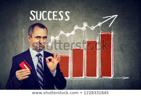 financial fraud concept liar dishonest businessman holding a credit card stock photo © ichiosea