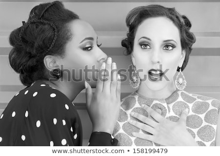 Photo of young african american woman talking secrets in ear of  Stock photo © deandrobot
