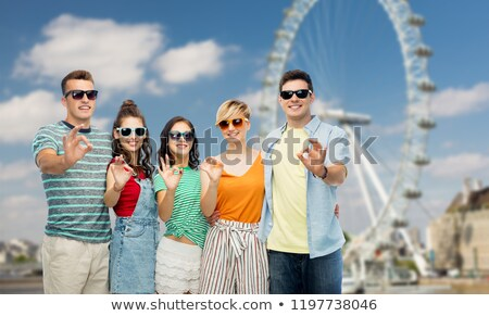 friends in sunglasses showing ok over ferry wheel Stock photo © dolgachov