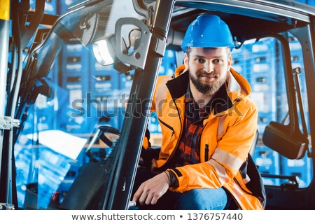 Worker in warehouse sitting in his forklift Stock photo © Kzenon
