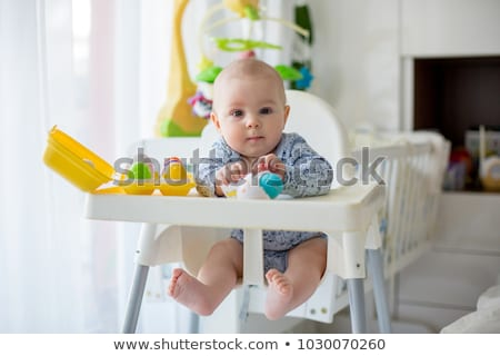 Adorable baby boy in the living room with bed on the back Stock photo © Lopolo