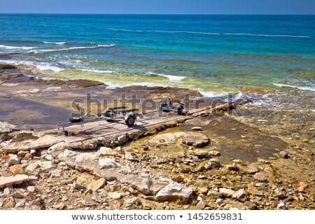 boat trailer by the sea on stone beach view stock photo © xbrchx