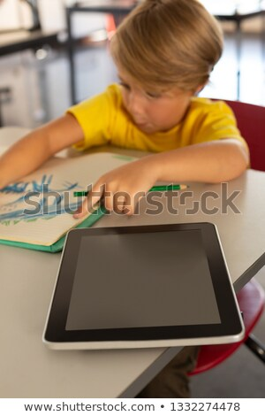 Front view of schoolboy drawing on notebook at desk in classroom of elementary school Stock photo © wavebreak_media