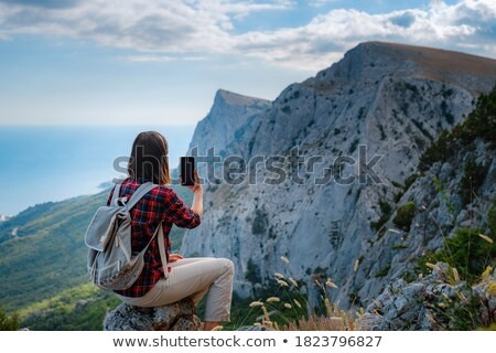 Hiker with backpack relaxing on top of the mountain. Ecotourism concept image, with happy female hik Stock photo © galitskaya