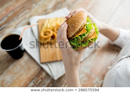 close up of woman eating hamburger at restaurant Stock photo © dolgachov