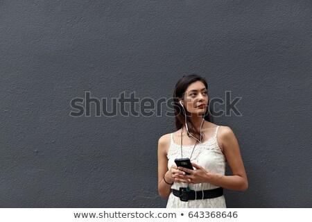 Brunette with headphones looking up against white background stock photo © wavebreak_media