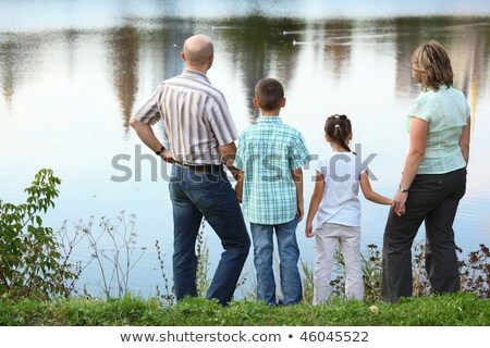 family in early fall park father mother little boy and girl is staying near pond stock photo © paha_l