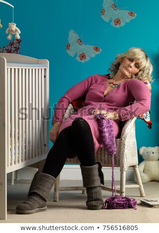 Mature woman asleep in chair next to cot Stock photo © IS2