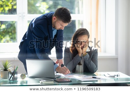 Businessman Explaining Graph To Sad Female Employee Stock photo © AndreyPopov