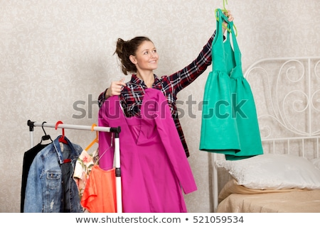 two pretty young women choosing clothes from new collection in d stock photo © boggy