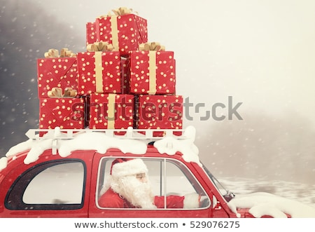 Santa Claus on a red car full of Christmas present with snowflakes background drives to deliver Stock photo © alphaspirit