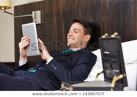 Empresário cama trabalhando comprimido quarto de hotel jovem Foto stock © tommyandone