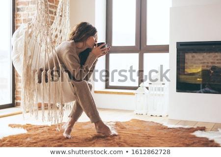 Stok fotoğraf: Beautiful Girl Is Warming Near Fireplace While