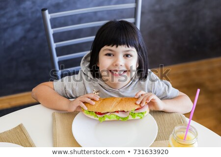 cute black hair little girl eating sandwich at home stock photo © boggy