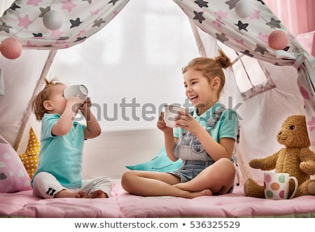 family playing tea party in kids tent at home Stock photo © dolgachov