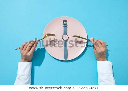 White plate with round whatch shows six o'clock served knife and fork in a girl's hands on a blue ba Stock photo © artjazz