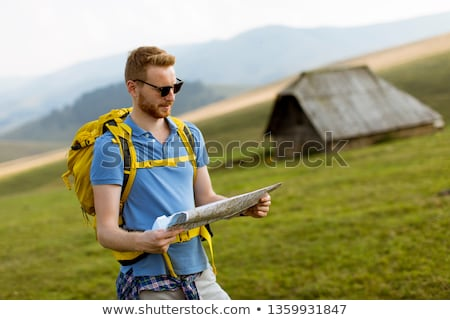 Young redhair man on mountain hiking holding a map Stock photo © boggy